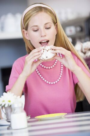Young woman sitting at a table eating a sweet treat Stock Photo