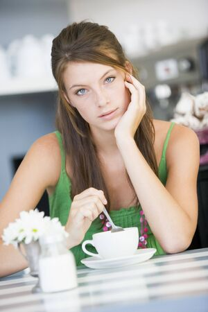 Young woman sitting at a table drinking tea photo