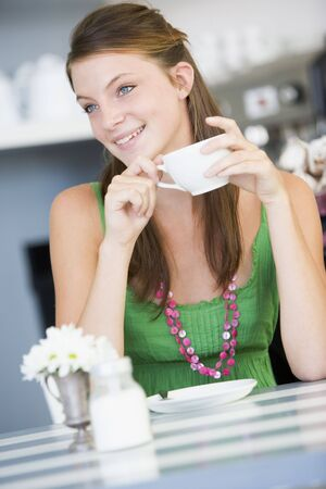Young woman sitting at a table drinking tea