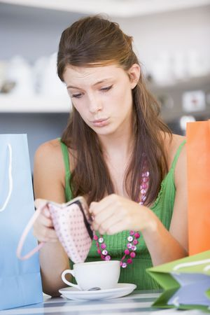 Young woman sitting at a table checking change purse photo