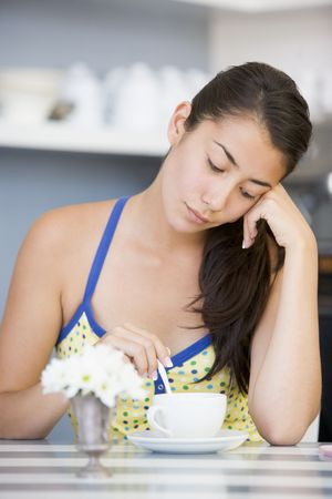 ambivalence: Jeune femme assise � une table boire du th�