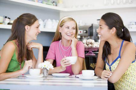 Tres j�venes mujer sentada en una mesa y bebiendo t�  photo