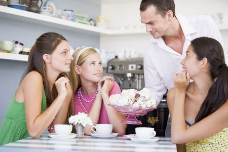 Man offering sweet treats to three young women photo