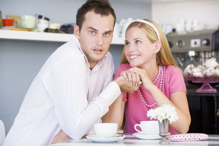 Young couple sitting at a table and having tea together