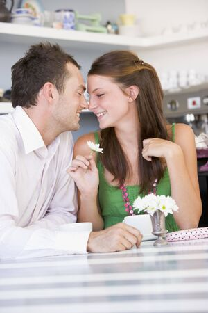 Young couple sitting at a table looking into each others eyes photo