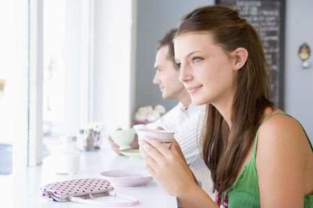 one person with others: Young couple having tea in a cafeteria Stock Photo