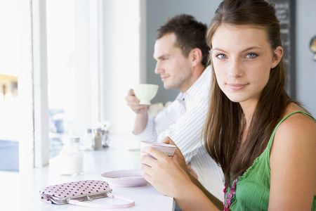 Young couple having tea in a cafeteria photo