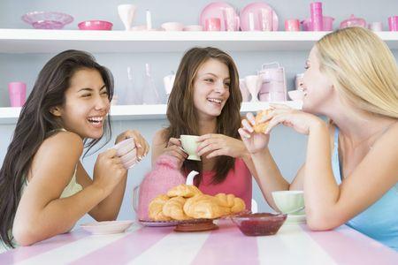 femme assise: Trois jeune femme assise � une table th� ayant et un snack