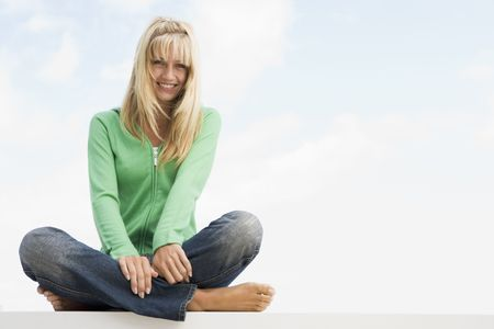 Blonde woman in a green sweater sitting outdoors photo