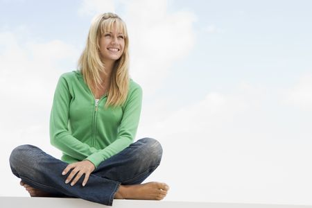 blond streaks: Blonde woman in a green sweater sitting outdoors
