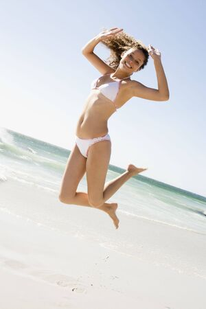 scanty clothing: Woman in a two piece bathing suit jumping on a beach