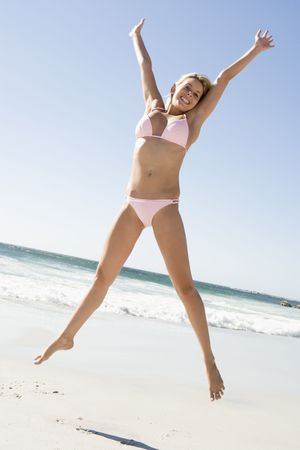 two piece bathing suit: Mujer en un dos piezas traje de ba�o saltando en una playa