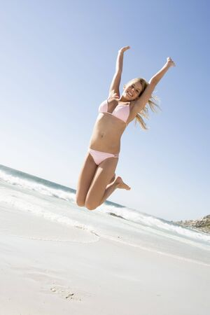 attired: Woman in a two piece bathing suit jumping on a beach