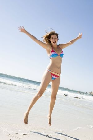 two piece swimsuits: Woman in a two piece bathing suit jumping on a beach