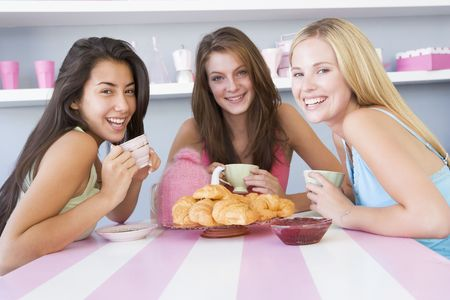 Three young woman sitting at a table having tea and a snack photo