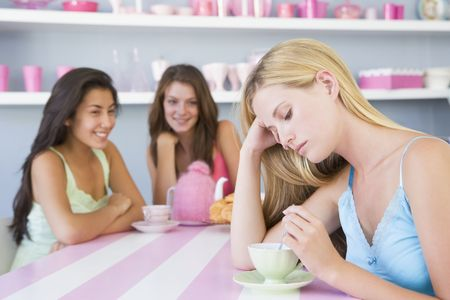 ambivalent: Young woman with a hangover sitting at a table with two friends
