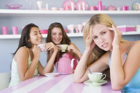 hangover: Young woman with a hangover sitting at a table with two friends