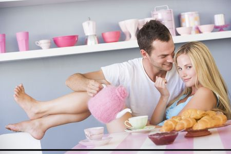 Young couple sitting at a table flirting and having tea photo