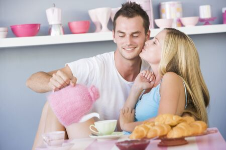 Young couple sitting at a table flirting and having tea Stock Photo - 3204145
