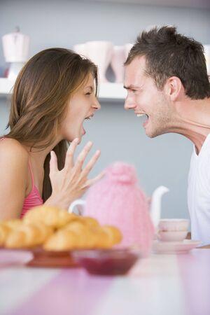 pareja discutiendo: Pareja joven sentado en una mesa discutiendo