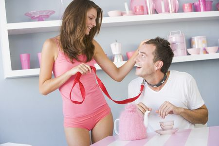 Young woman joking around with boyfriend on a leash Stock Photo