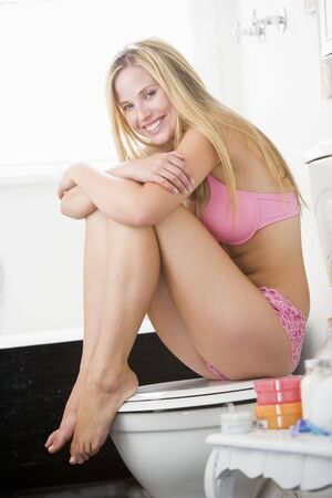 Woman sitting in bathroom photo