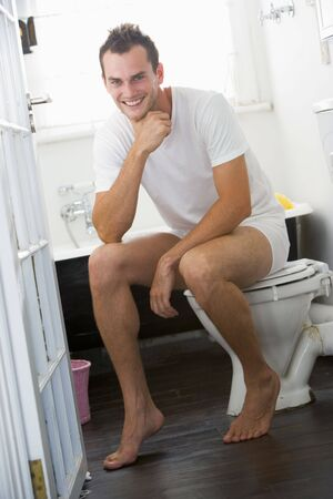 attired: Man sitting in a bathroom