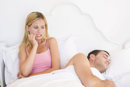 Young couple in bed having trouble sleeping photo