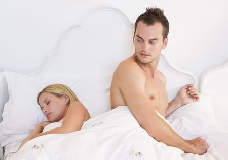 attired: Young couple in bed having trouble sleeping Stock Photo