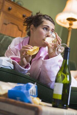 persona deprimida: Joven mujer en su casa bebiendo vino y comiendo papas fritas