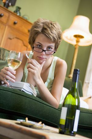 looking towards camera: Young woman at home smoking and drinking wine by telephone