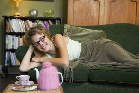 Young woman lying on sofa at home photo