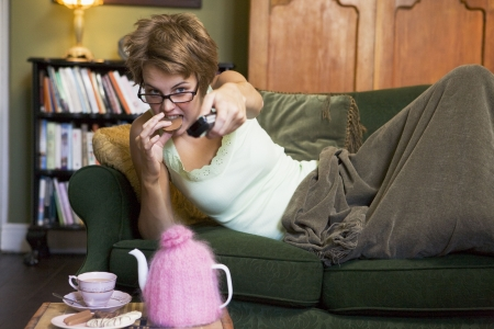 lying on couch: Young woman lying on sofa at home eating cookies and watching television