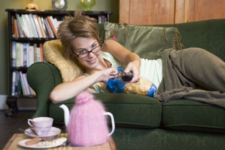 snacking: Young woman lying on sofa at home eating potato chips and watching television