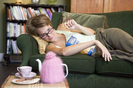 Young woman lying on sofa at home eating potato chips photo