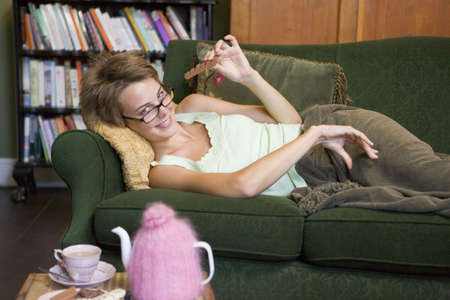 Young woman lying on sofa at home eating chocolate photo