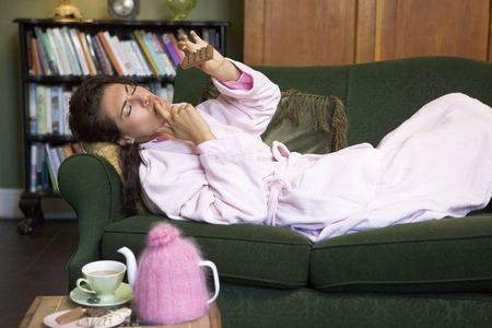 tea breaks: Young woman lying on sofa at home eating chocolate