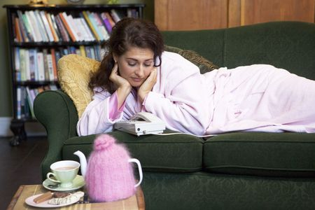 Young woman lying on sofa at home watching telephone Stock Photo - 3204514