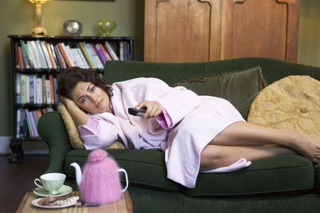 robe: Young woman lying on sofa at home watching television Stock Photo