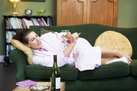 tea breaks: Young woman lying on sofa at home smoking and drinking wine Stock Photo