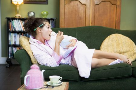 Young woman lying on sofa at home eating a sweet treat photo