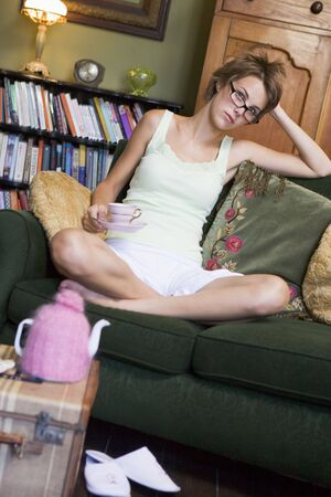 Young woman sitting on sofa at home drinking tea photo