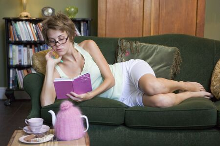 saddened: Young woman lying on sofa at home writing in her diary