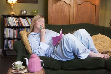 tea breaks: Young woman lying on sofa at home writing in her diary