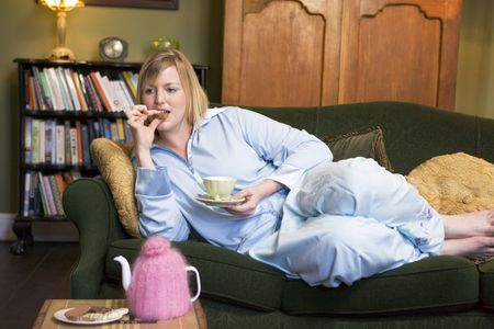 Young woman lying on sofa at home eating cookies and drinking tea photo