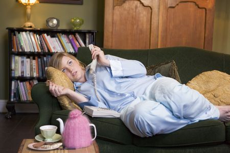 Young woman lying on sofa at home holding telephone photo