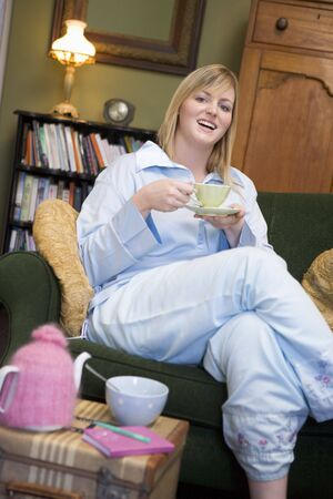 indulging: Young woman sitting on sofa at home drinking tea