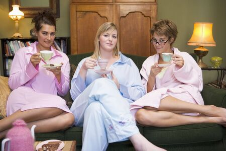 Three woman in night clothes sitting at home drinking tea Stock Photo
