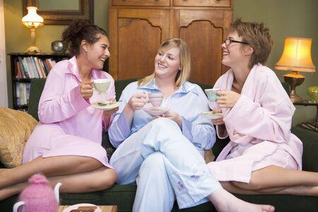 pijamada: Tres mujer en ropa de noche sentado en su casa bebiendo t�  Foto de archivo