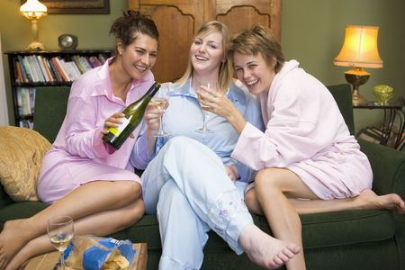 Three woman in night clothes sitting at home drinking wine photo